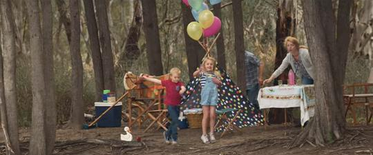 Still from Cargo 2017 of a family on the shore. Two girls wave towards the camera. Ballons and mom and dad are in the background.