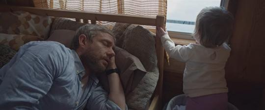 Still from Cargo 2017 of Andy (Martin Freeman) laying in a bed with his baby daughter.