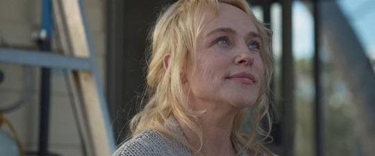 Still from Cargo 2017 of Kay (Susie Porter) looking up towards the sky and smiling.