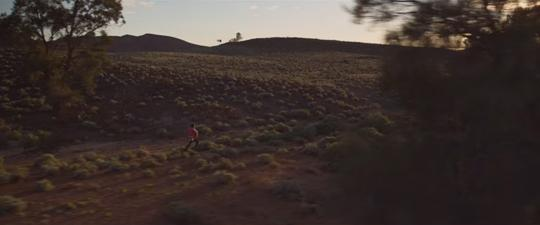 Still from Cargo 2017 of Thoomi (Simone Landers), a quirky young girl with a grand imagination, running along a path.