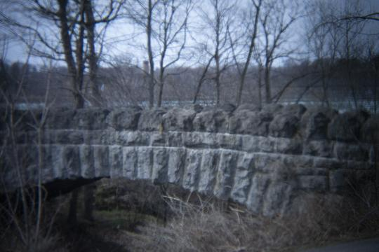 Stone bridge in Niagara Falls State Park Goat Island and Three Sisters Islands. The photo is of an old stone bridge surrounded by bare trees.