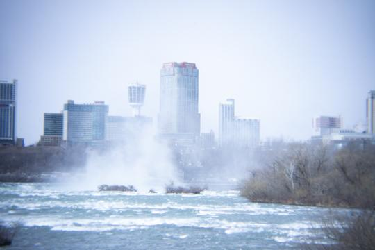 A photograph of the crest of Niagara falls with Canada in the background as seen from Goat Island and Three Sisters Islands in Niagara Falls State Park by Laura Chenault.