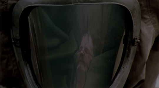 Still from Outbreak (1995) of a victim in the face mask of a scientist