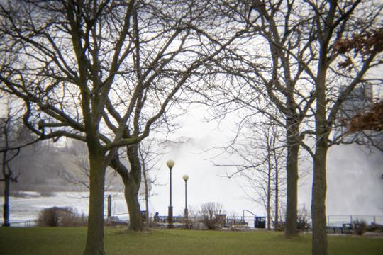 A photo of trees with the mist from NIagara Falls in the backgroun of an empty park by Laura Chenault – Exploring Prospect Point at Niagara Falls State Park