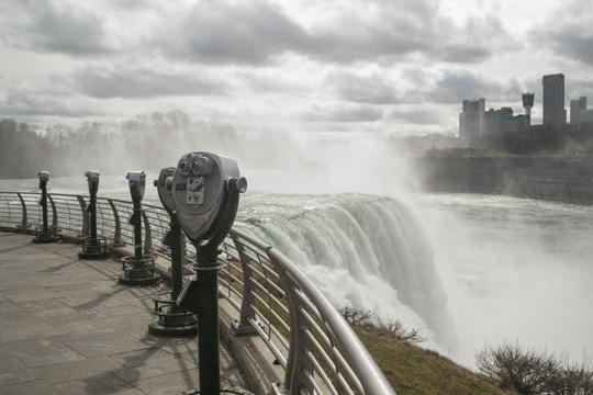 A photo of water flowing over the crest of Niagara Falls with coin operated binoculars in the foreground by Laura Chenault – Exploring Prospect Point at Niagara Falls State Park