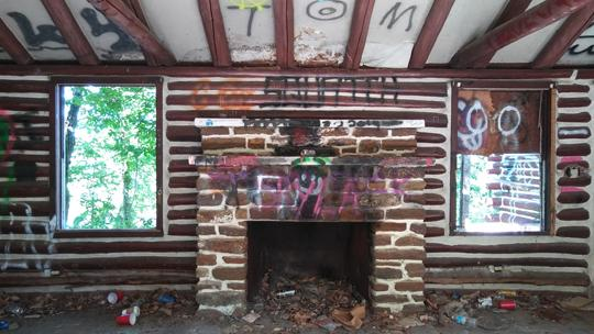 A photo of a brick fireplace, flanked by two windows in an abandoned log cabin. Exploring an abaondoned cabin in Rancocas State Park by Laura Chenault