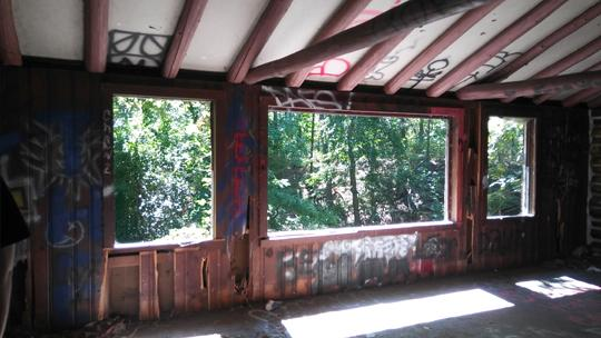 A view of the woods outside through three large, glassless windows in an abandoned log cabin. Exploring an abaondoned cabin in Rancocas State Park by Laura Chenault