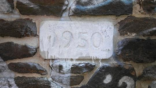 A photo of a stone engraved with 1950 surrounded by red bricks on an abandoned log cabin. Exploring an abaondoned cabin in Rancocas State Park by Laura Chenault
