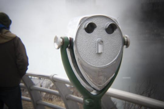 Photo of a coin operated binocular in the foreground and part of a person in the background by Laura Chenault – Exploring Terrapin Point at Niagara Falls State Park