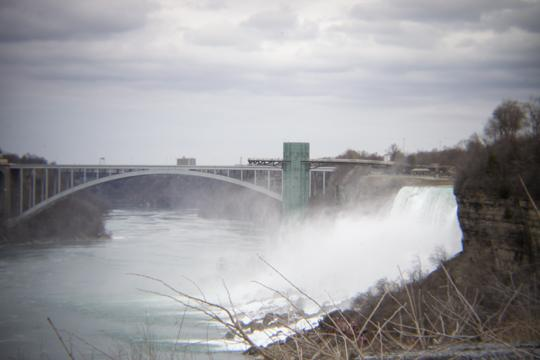 Photo of modern bridge with a small waterfall to the right by Laura Chenault – Exploring Terrapin Point at Niagara Falls State Park