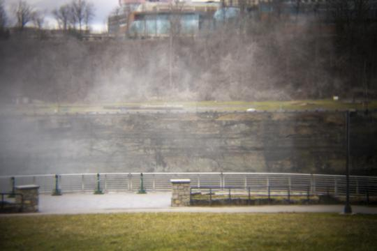 Photo of a brick building in the background partially obscured by the mist off the falls by Laura Chenault – Exploring Terrapin Point at Niagara Falls State Park