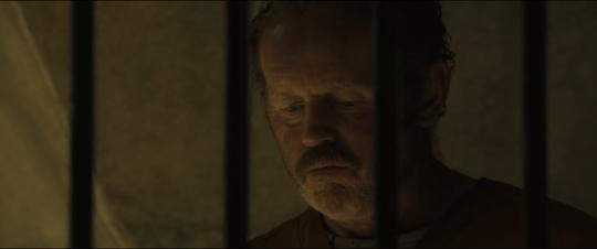 Still from World War Z: Quarantine Cinema of David Morse as an Ex-C.I.A. agent in a cell.