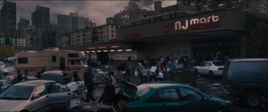 Still from World War Z: Quarantine Cinema of people panicking in the parking lot of a grocery store called NJ Mart.