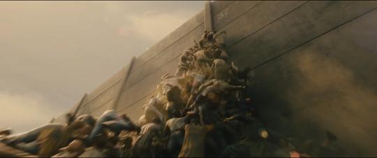 Still from World War Z: Quarantine Cinema of zombies swarming up a high wall.