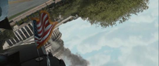 A still from Zombieland (2009): Quarantine Cinema showing the American Flag waving in front of a burning building.