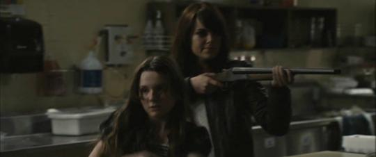 A still from Zombieland (2009): Quarantine Cinema when we meet Wichita and Little Rock. They are standing back to back and defensively holding guns.