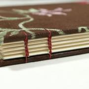 Spine of brown embroidered coptic stitch book by Laura Chenault