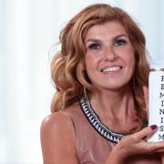 Tge Still from Connie Britton's Hair Secret Video has the star holding a bottle labelled feminism.