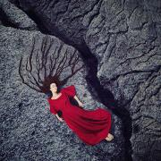 Self portrait by Kylli Sparre of a woman in a red dress laying on a rock next to a crack. Her hair is spread out and looks like tree roots.
