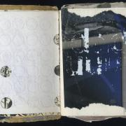 "DDD: Random Journal Page 163 by Laura Chenault. This sketchbook spread has a white perforated left side with some of the holes punched out to reveal a map underneath. The white side is a blue and gray with deteriorating transfer letters ""ddd"" and ""uuu"" in white ink."