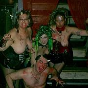 Sister Nagsters at the Double Door, Chicago IL with Dagon Bytes and Mistress Cherish is of four people. In the background are three corsetted women dressed like medusa and crouching down in front of them is a topless man dressed like Pan